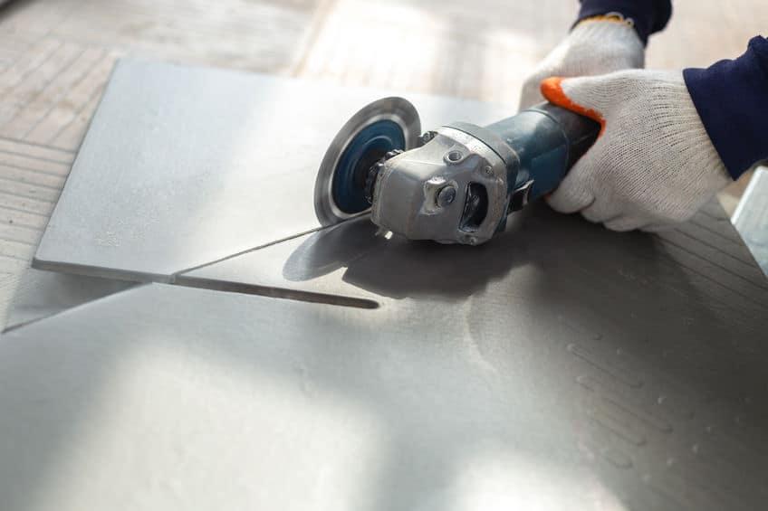 Werknemer snijden een tegel met behulp van een haakse slijper op de bouwplaats