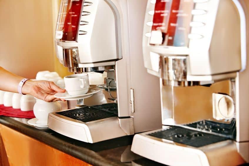 koffiemachine met vrouwelijke hand en kopje koffie.