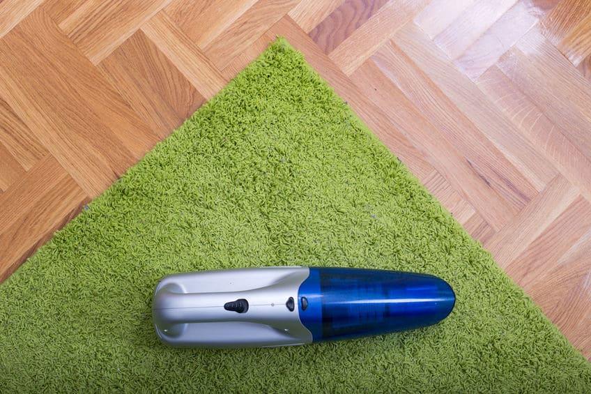 Handstofzuiger op het tapijt