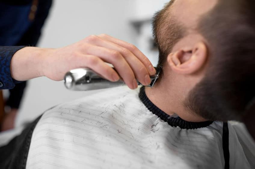 man en kapper met trimmer snijden baard bij salon