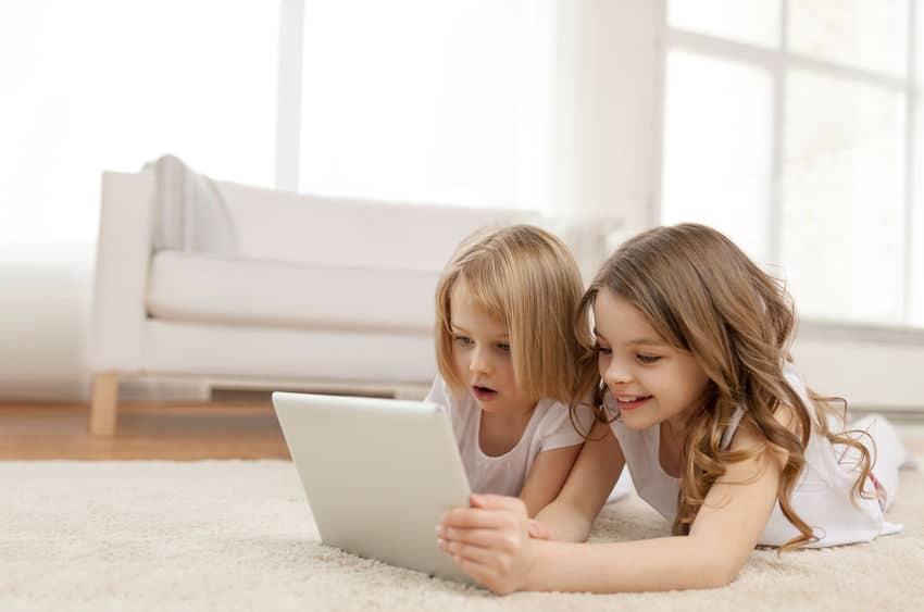 twee kleine meisjes met tabletpc thuis