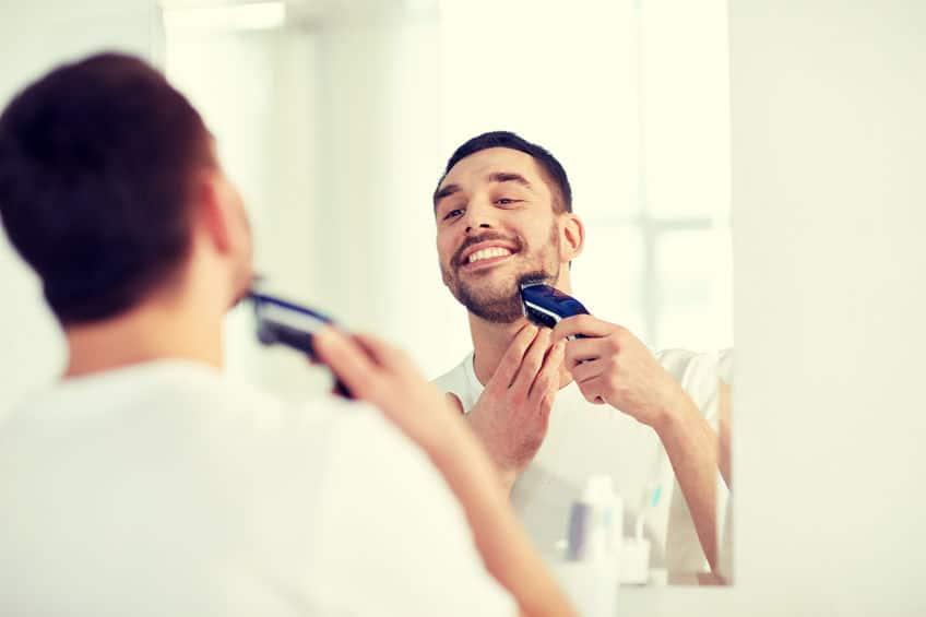 man scheren baard met trimmer op badkamer