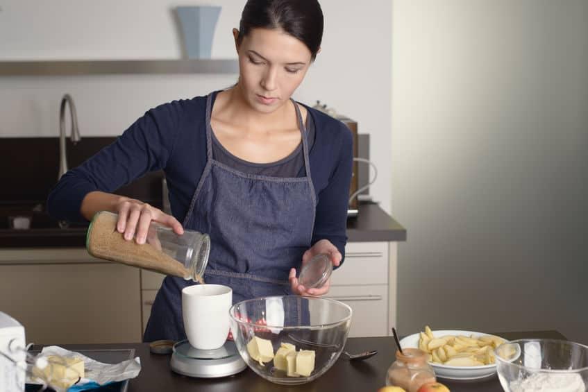 Jong huisvrouwenbaksel in de keuken