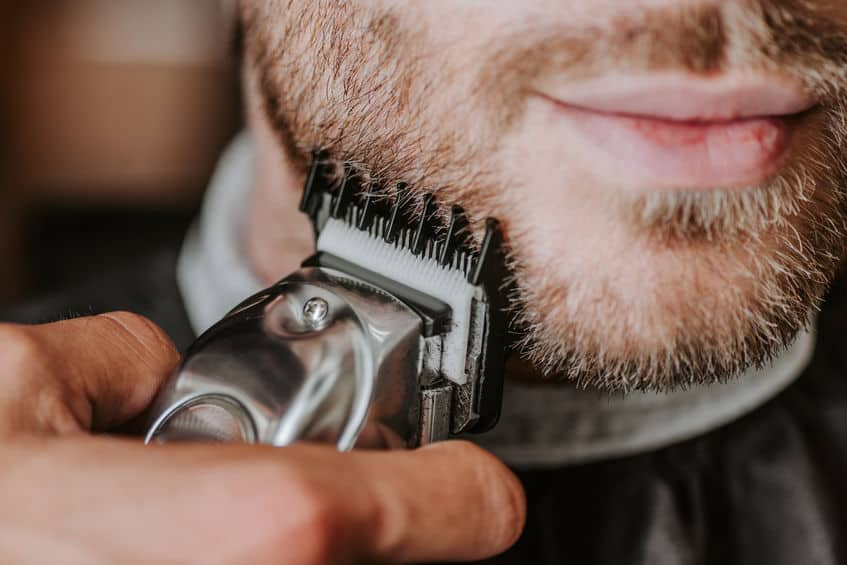 close-up van kapper bedrijf trimmer tijdens het scheren man