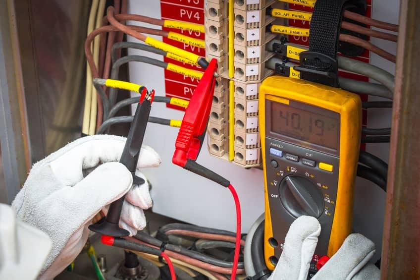 Elektricien, elektricien die de digitale multimeter gebruikt om de weerstand en spanning van elektrische systemen in de olie- en gasindustrie te controleren.