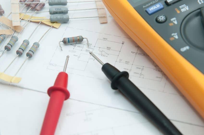 circuit controleren door meerdere meter. elektrotechnisch ingenieur tijdens het controleren van de printplaateenheid met een multimeter.