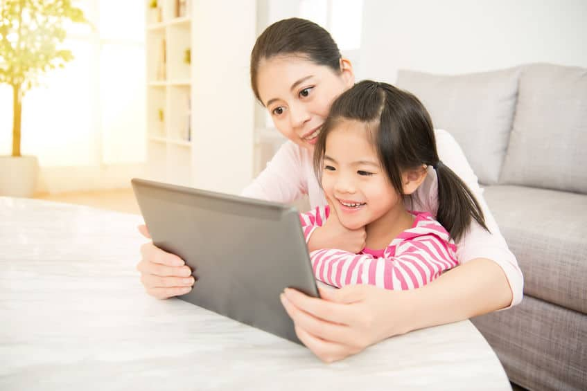 moeder en dochter die in digitale tablet kijken