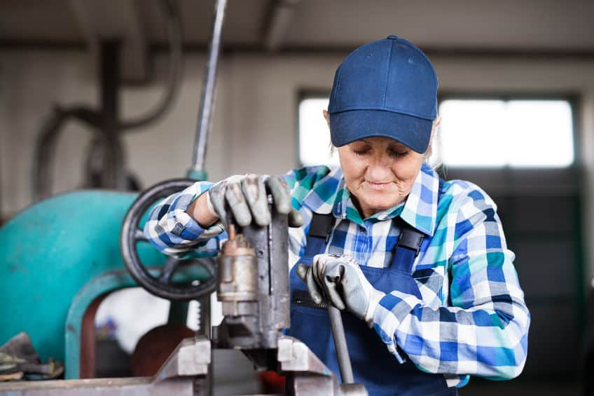 Senior vrouwelijke monteur die een auto repareert in een garage.