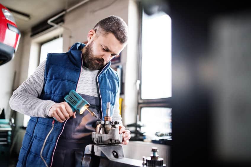 Menselijke monteur die een auto repareert in een garage.