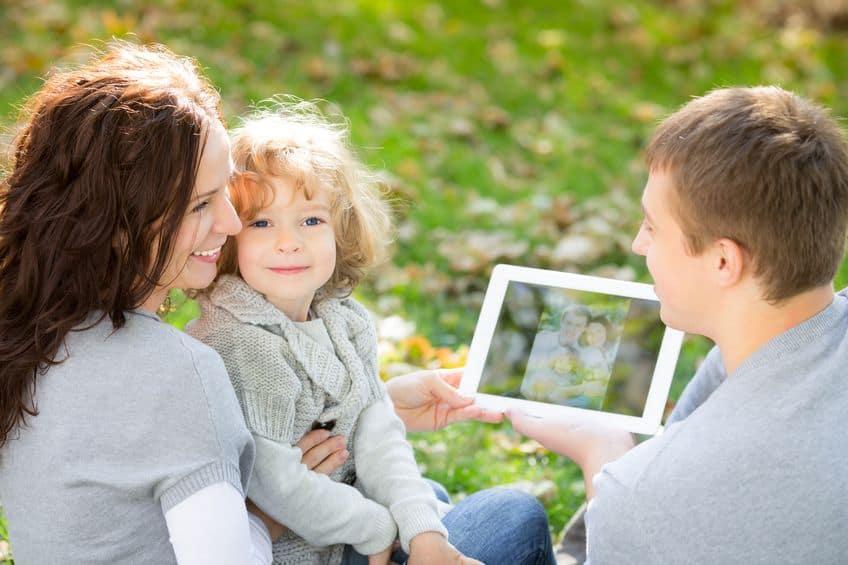 gelukkige familie met behulp van tablet-pc buiten in herfst park
