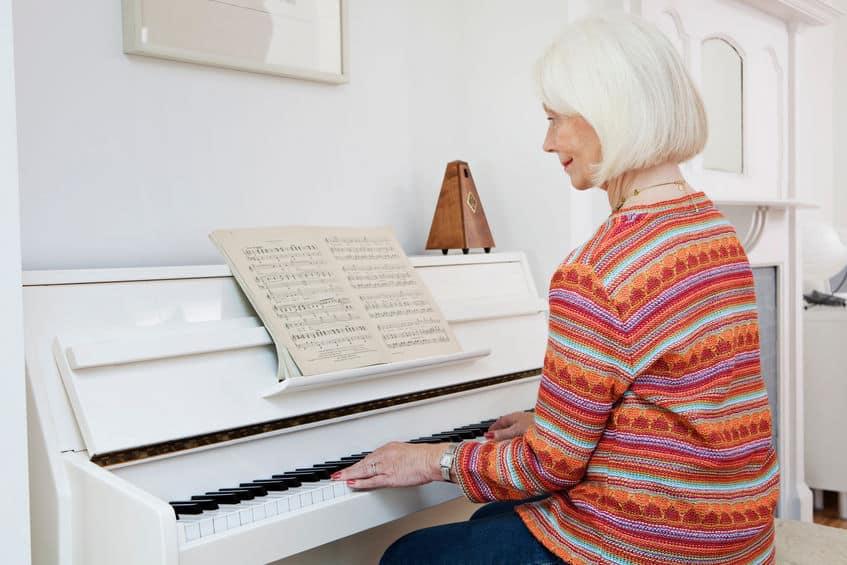 Een senior vrouw piano spelen