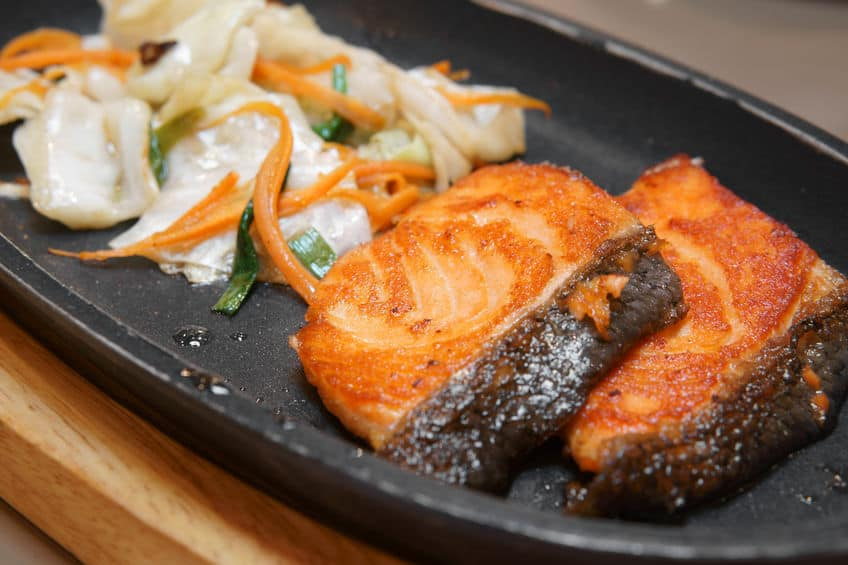 heerlijk Teppanyaki zalmgrill eten met groente in de ijzeren pan en houten snijplank op tafel in Japans restaurant voor lunch of diner