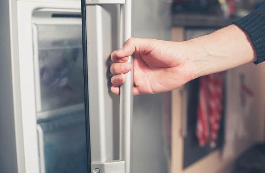de hand van een jonge man opent de deur van een vriezer