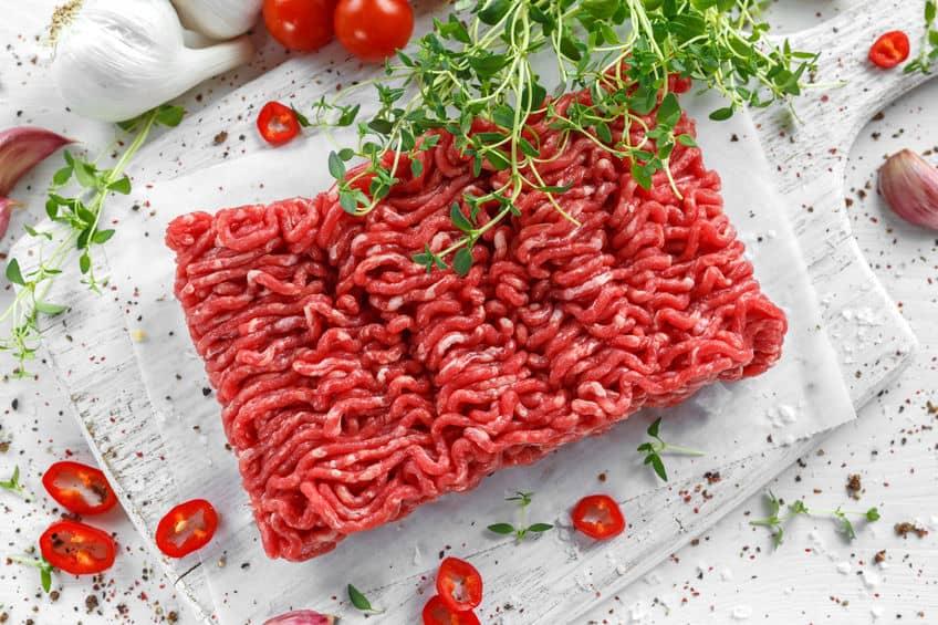 Vers rauw rundvlees gehakt met zout, peper, Spaanse peper en verse tijm op wit bord.