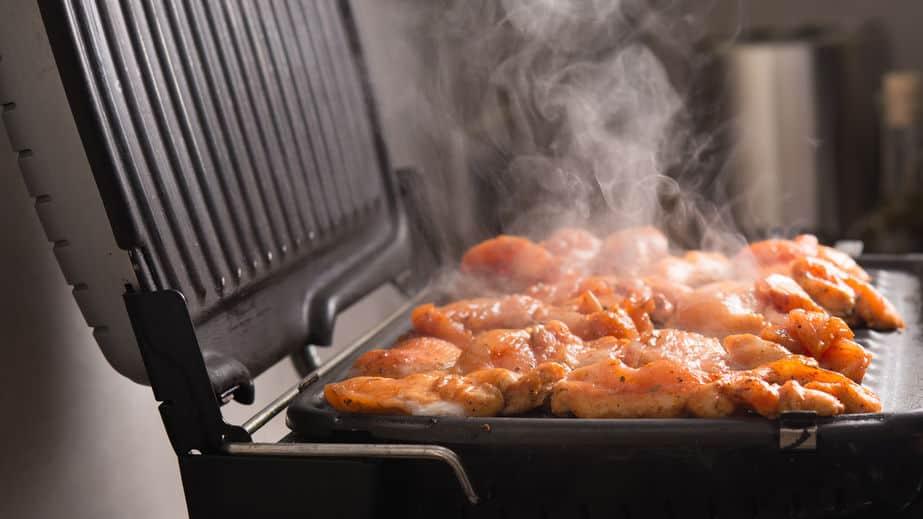 Close-up van hete kokende kipfilet op de elektrische grill