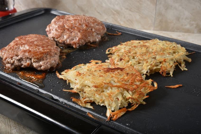 Koken worstpasteitjes en opgebakken aardappels op een elektrische grill.