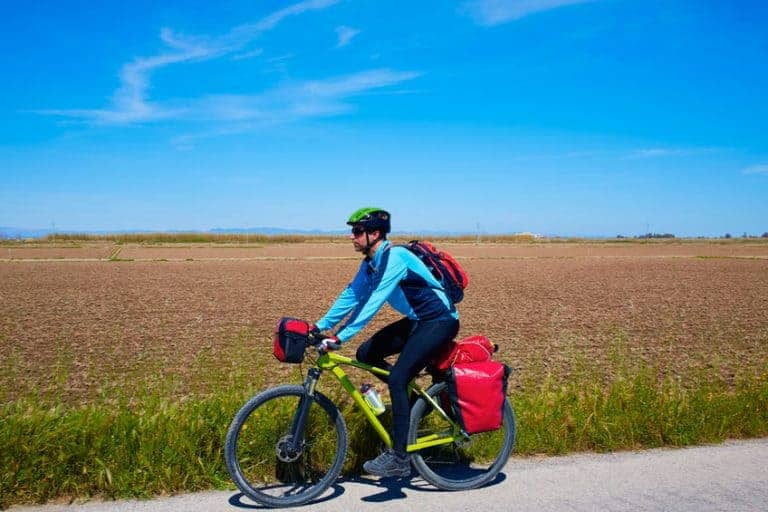 man met fiets en koffers