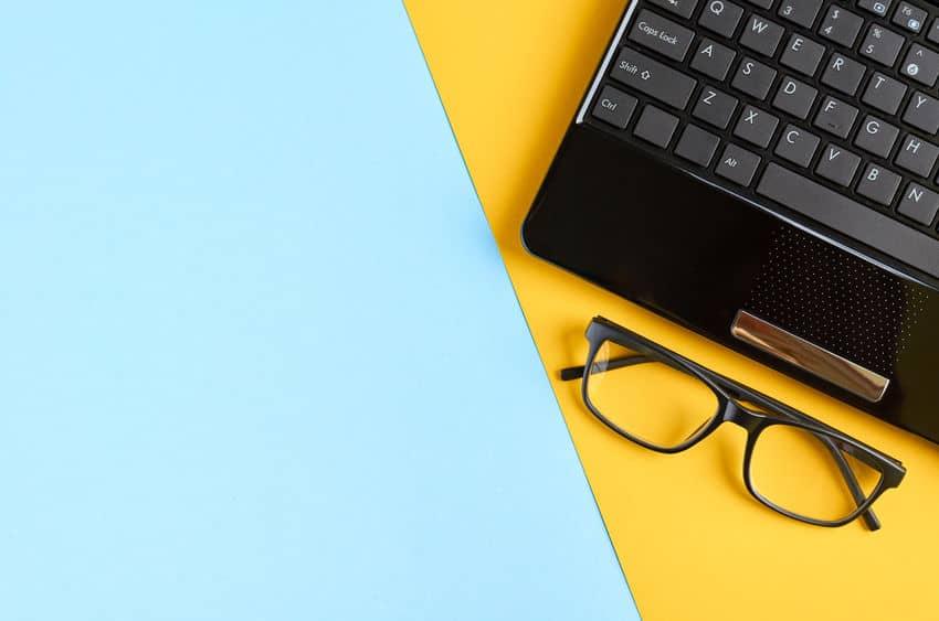 computer en bril op blauwe achtergrond