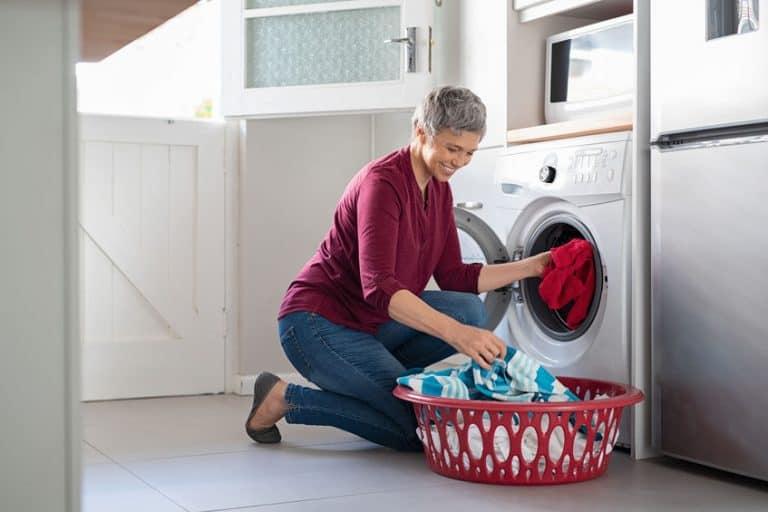 vrouw die de kleren in een droger zet
