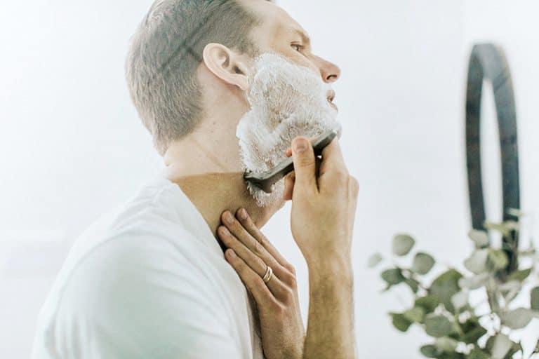 Mann rasiert sich mit Rasierschaum