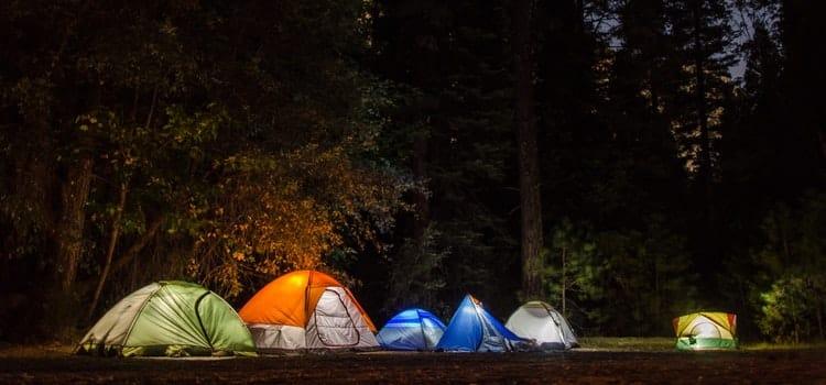 Mehrere erleuchtete Zelte im Wald