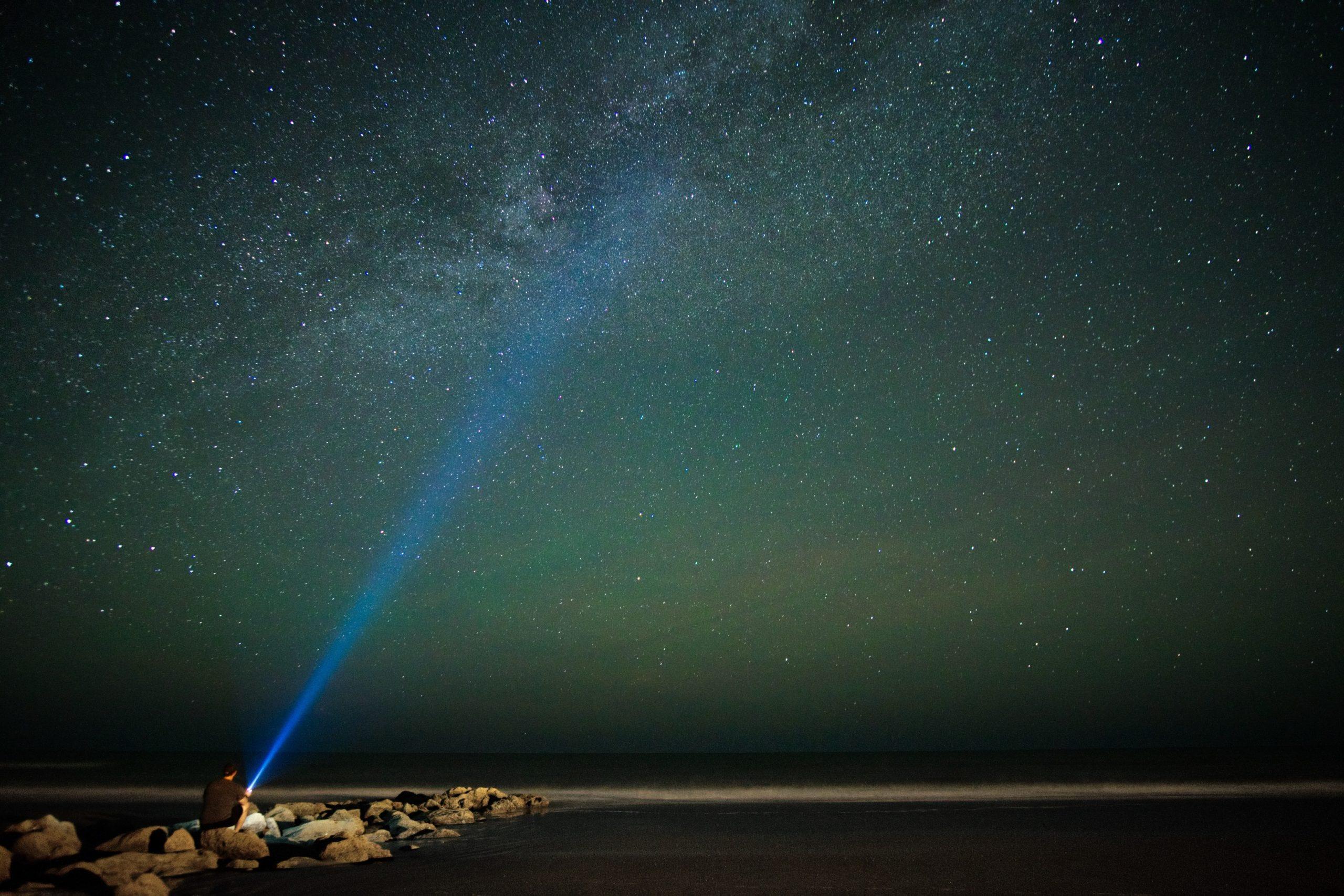 Na foto um homem sentado na beira do mar com uma lanterna acesa.