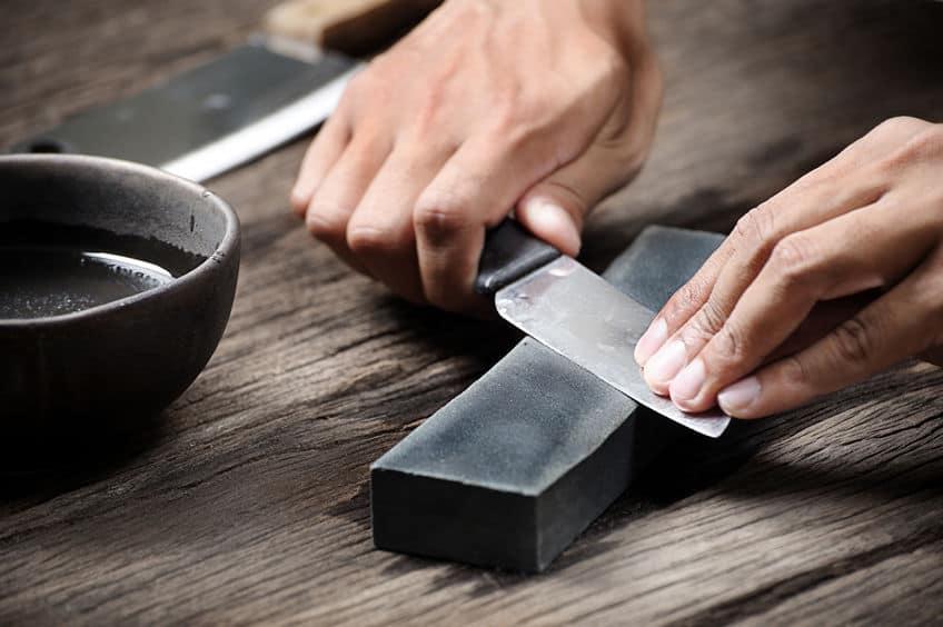 Faca sendo afiada em pedra de amolar.