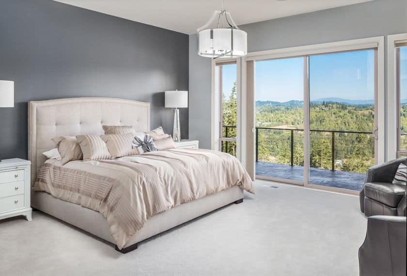 Imagem de um quarto com cama feita e edredom bege.