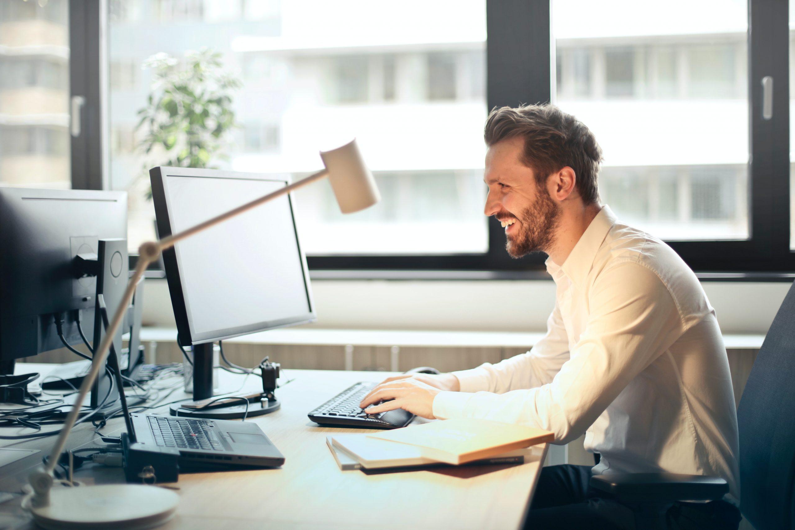 Na foto um homem sorrindo sentado em um escritório.