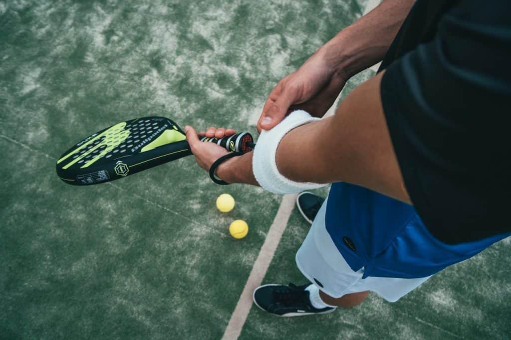 Imagem destaca mãos de um jogador que segura uma raquete de padel.