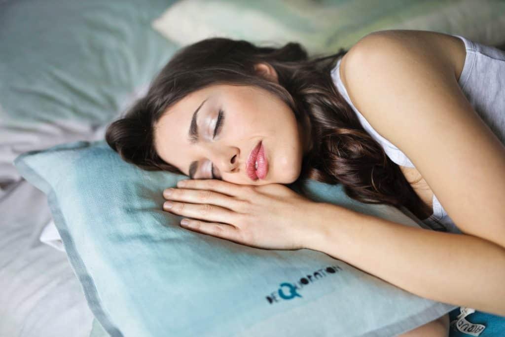 Foto de uma mulher morena, maquiada, dormindo em cima de um travesseiro azul claro.