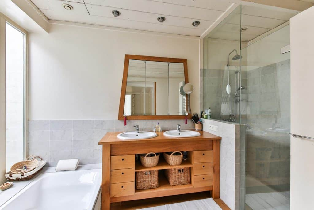 Na foto um banheiro com armários e espelho em madeira, uma banheira branca no lado esquerdo e um box de vidro no lado direito.