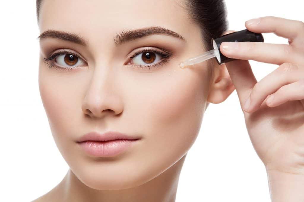 Mulher passando retinol em óleo no rosto.