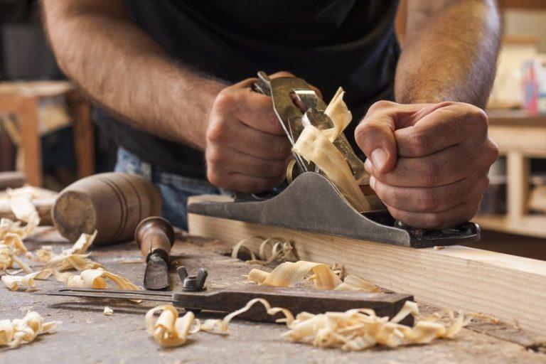 mãos de homem manuseando uma plaina em pedaço de madeira sob uma bancada com outras ferramentas e lascas de madeira.