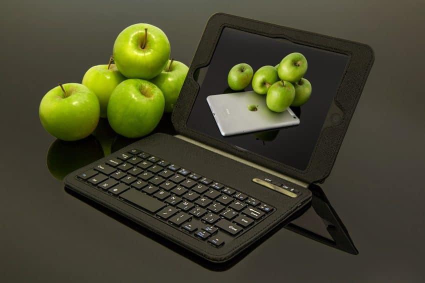Imagem mostra um tablet com teclado com maçãs verdes ao lado e na tela do equipamento.
