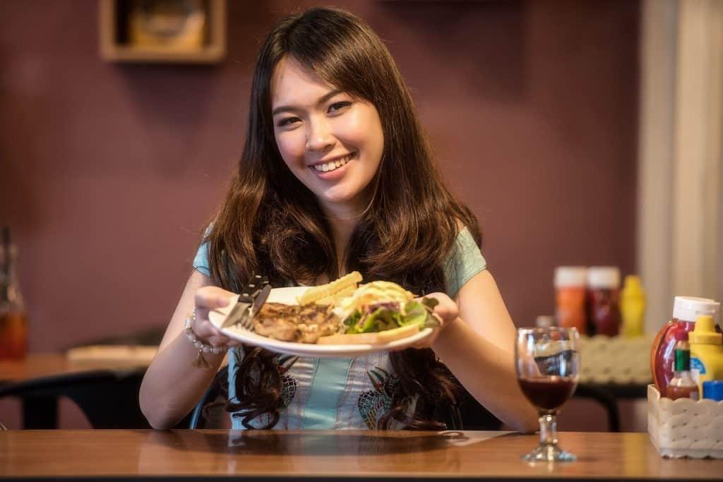 mulher segurando prato e sorrindo para a câmera