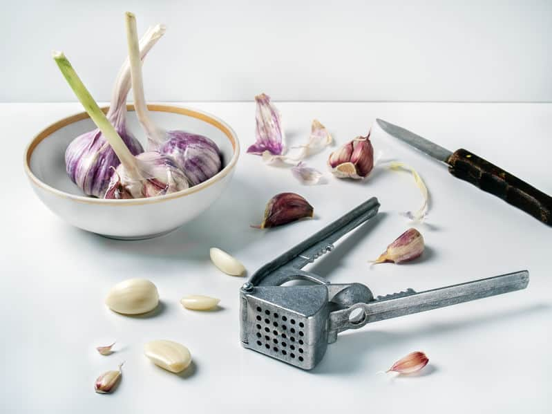 Imagem de espremedor de alho sobre mesa com alho e faca ao lado.