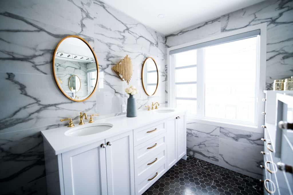 Na foto um banheiro com duas pias e armários brancos com torneiras douradas.