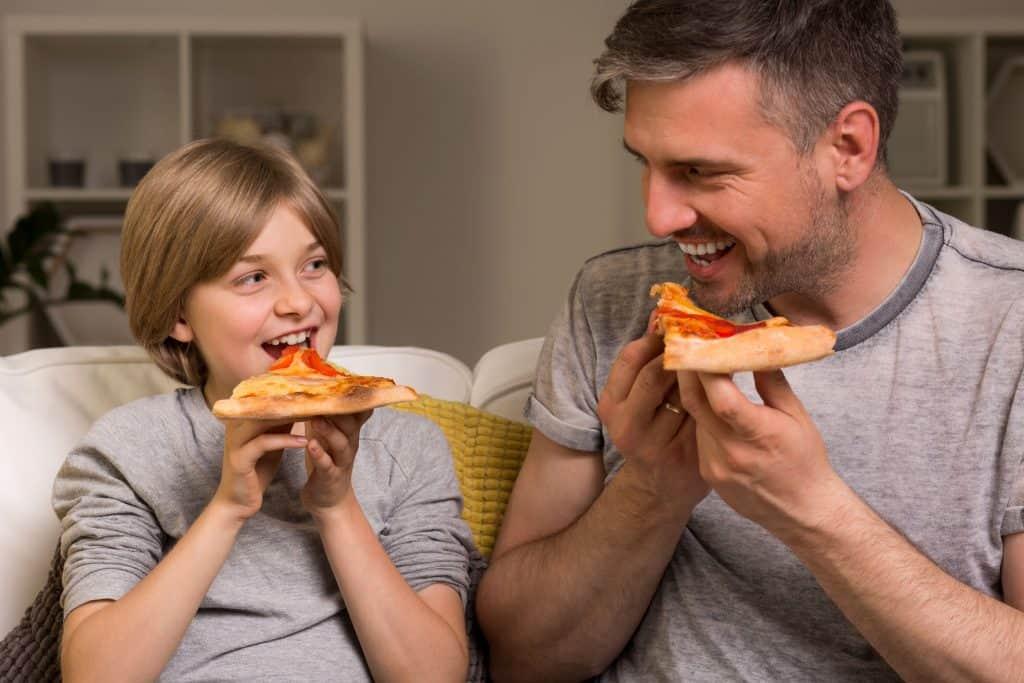 Pai e filho comendo pizza juntos.