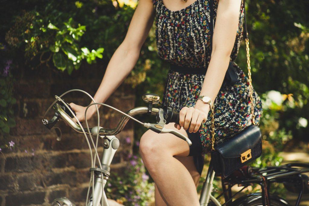 Moça andando de bicicleta com mãos no guidão
