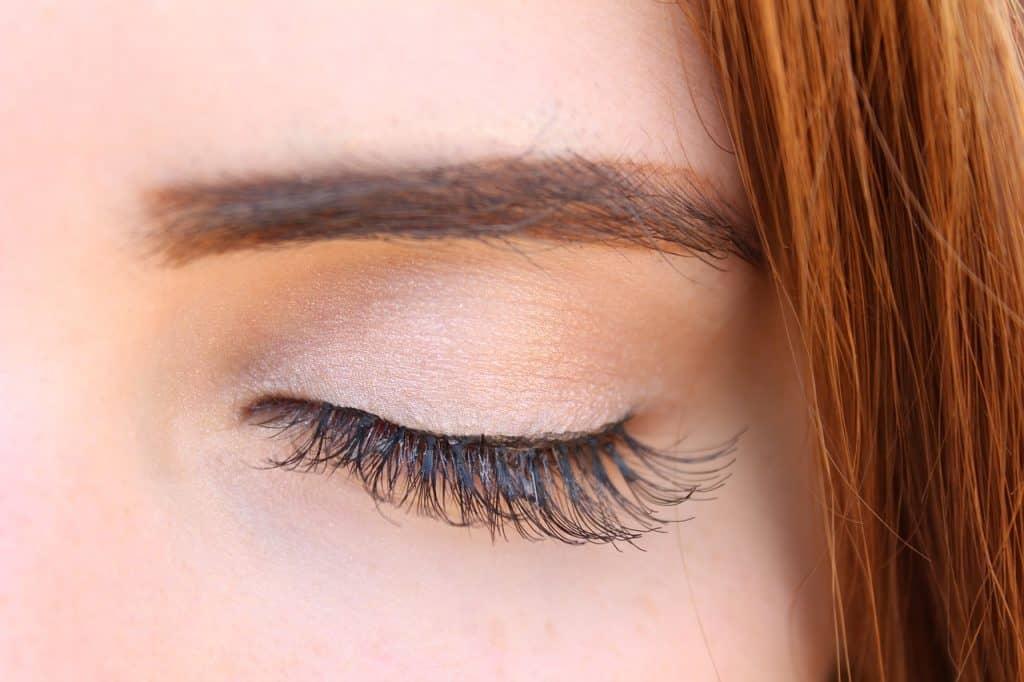 Imagem dos olhos de uma mulher com cílios postiços aplicados.
