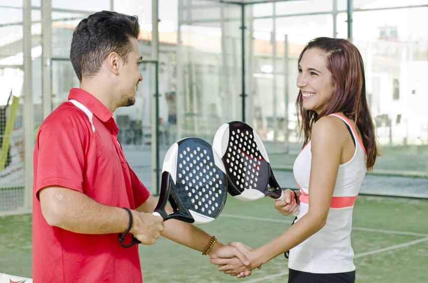 Imagem mostra um homem e uma mulher segurando suas raquetes de padel e se cumprimentando durante uma partida de padel.