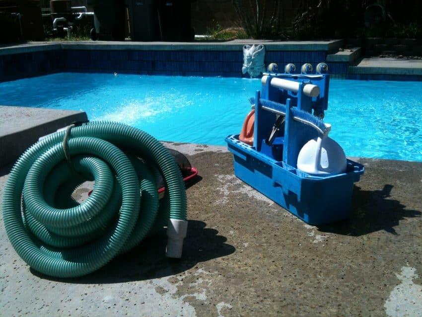 Imagem mostra mangueira e kit de limpeza na borda de uma piscina.