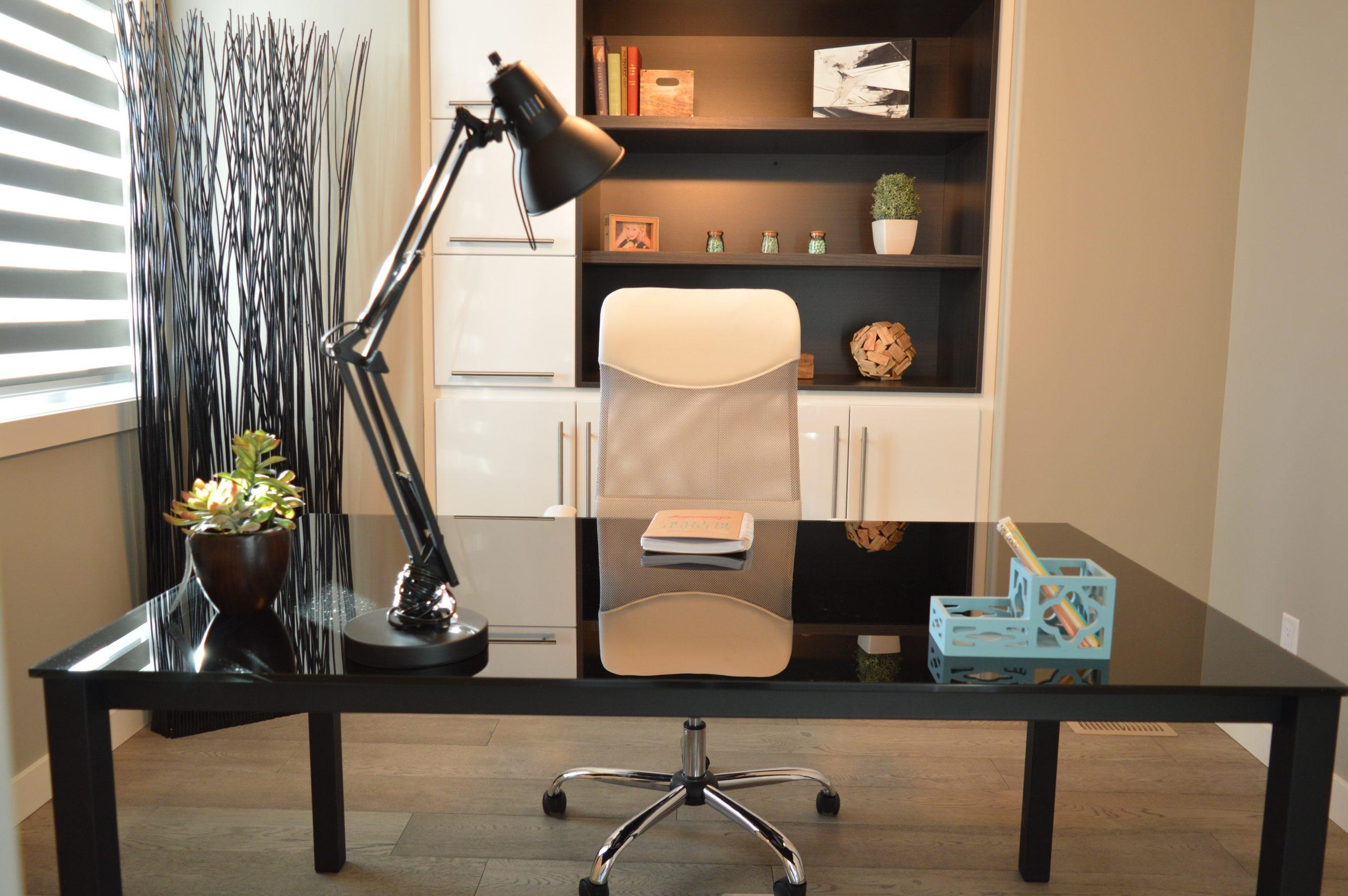 Na foto uma luminária em cima de uma mesa em um escritório.