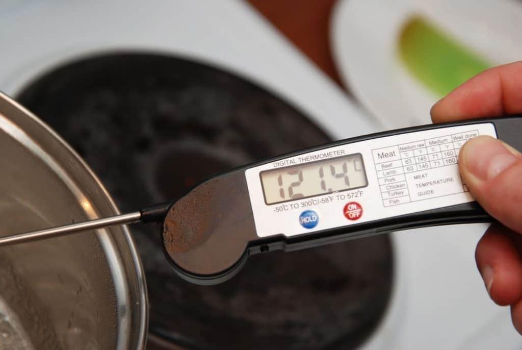 Imagem de uma mão segurando um termômetro culinário digital em uma panela.
