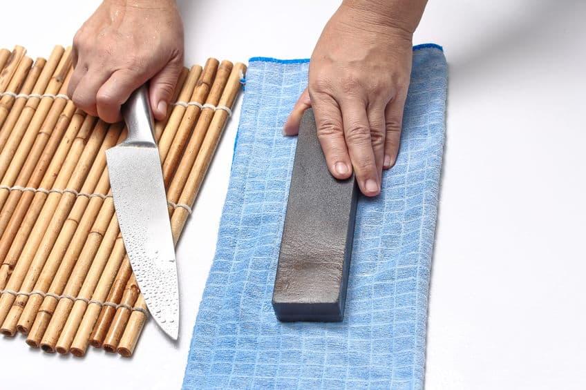 Imagem de pessoa segurando faca sobre mesa com pedra de amolar ao lado.