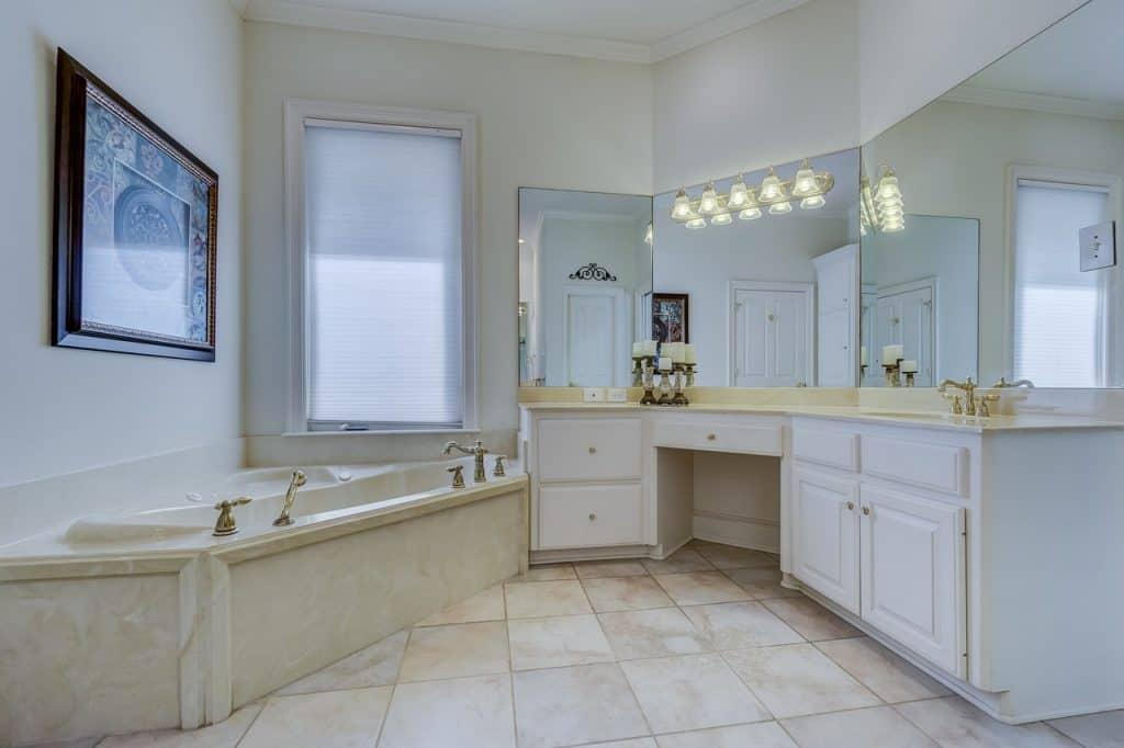 Na foto um banheiro com banheira ao lado esquerdo e uma bancada com pias, espelhos e armários do lado direito.