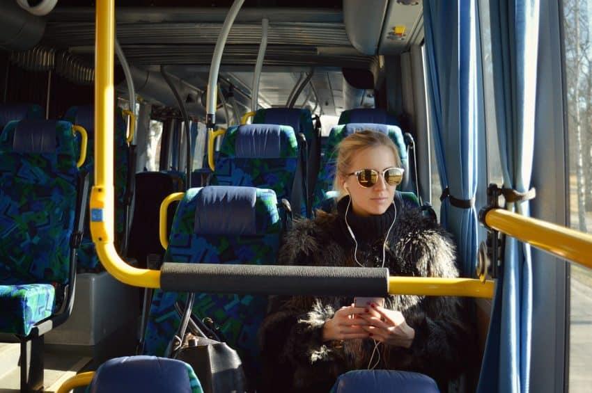 Mulher no ônibus com fone de ouvido.