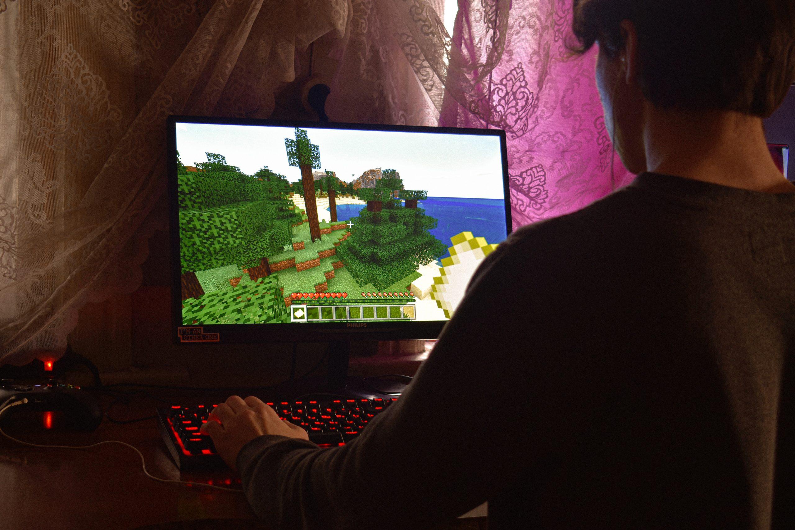 Jovem jogando em um computador gamer dentro do quarto
