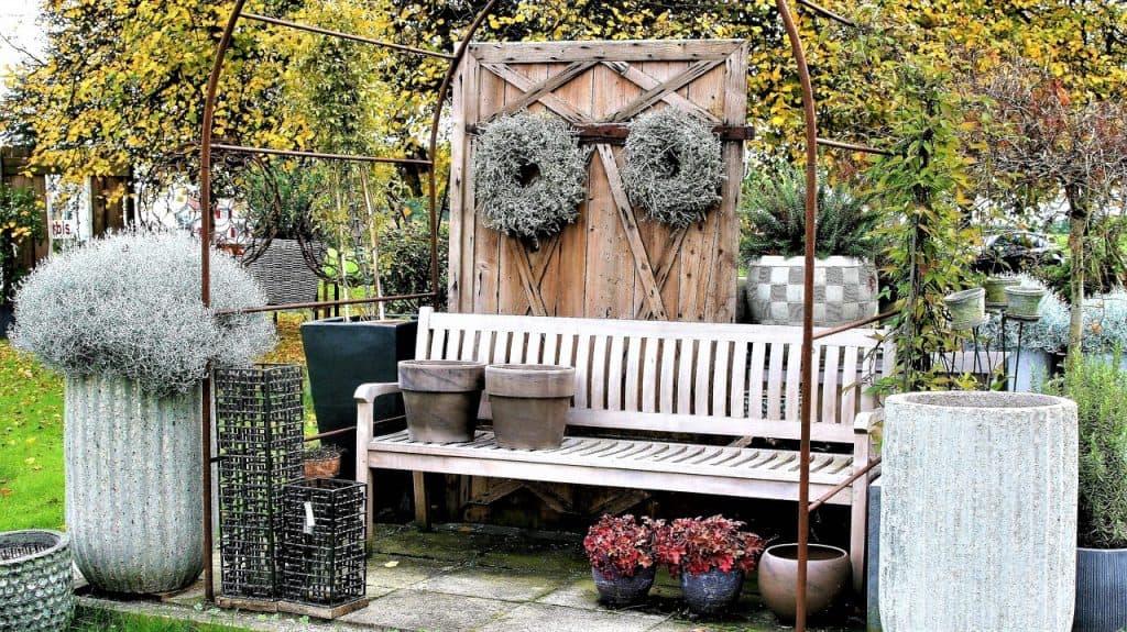 Banco de jardim de madeira branca em meio a decorações e plantas.